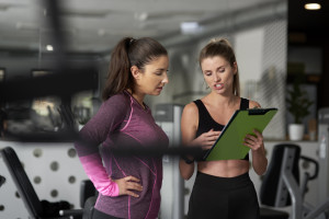 Personal trainer guiding young woman